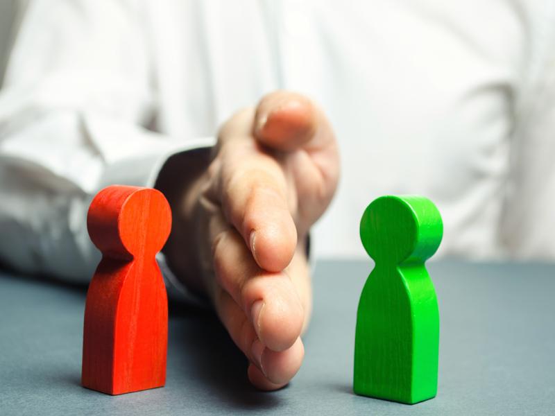 Un homme d'affaires séparant deux personnages en bois, un rouge et un vert, de la main.