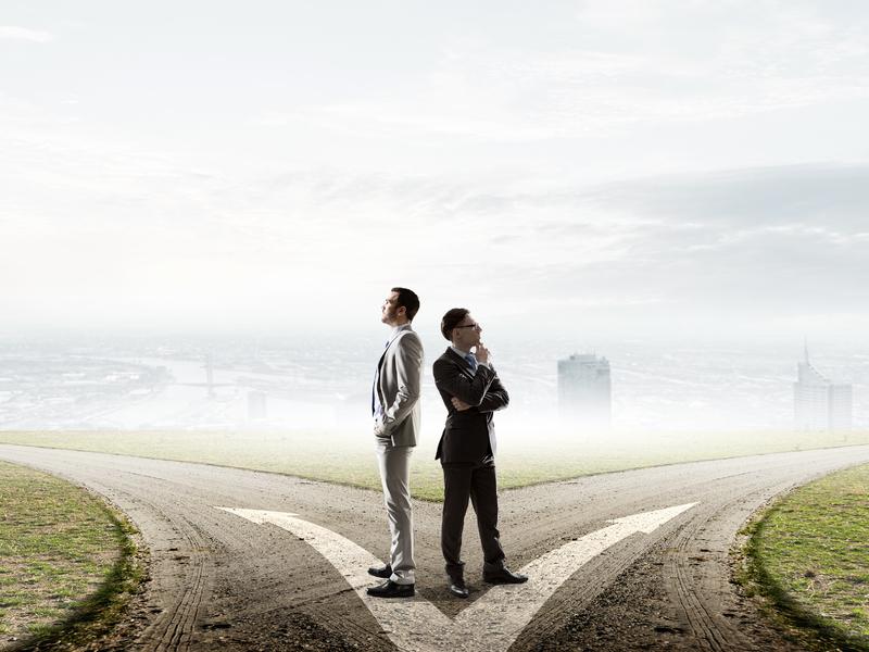 Deux hommes d'affaire dos à dos devant un chemin qui se divise en deux, l'air pensif.