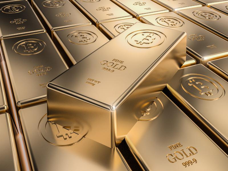 Un lingot d'or posé sur une plaque de lingots d'or. Sur chacun est gravé le B de bitcoin.