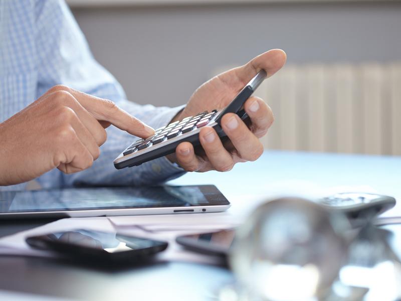Un homme d'affaires à son bureau tapant sur une calculatrice.