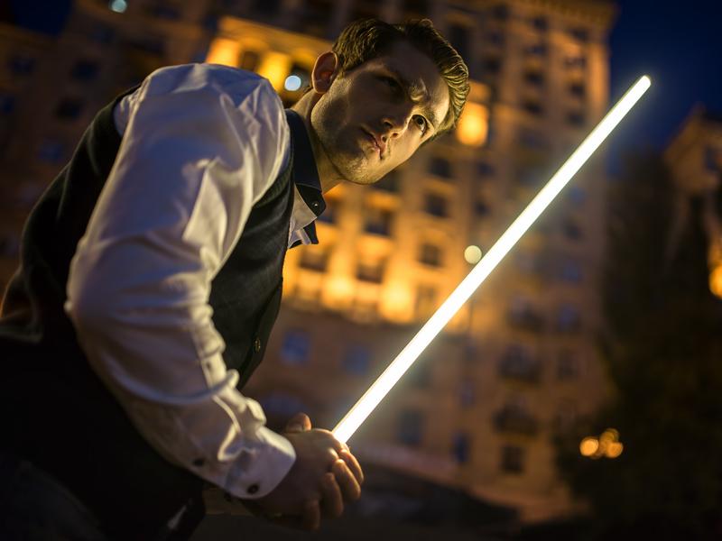 Un homme d'affaire en pleine nuit devant un immeuble. Il tient un sabre laser.