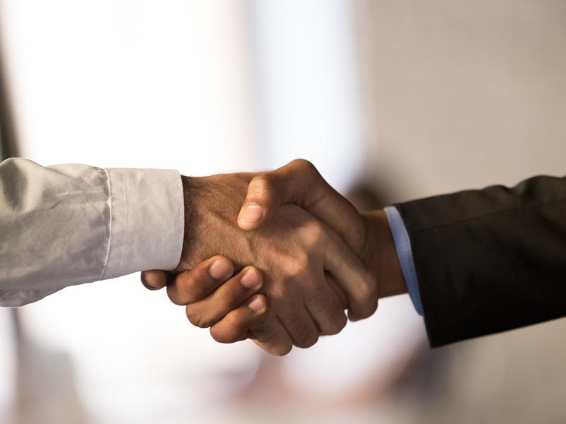 Deux hommes d'affaires qui se serrent la main dans un immeuble.