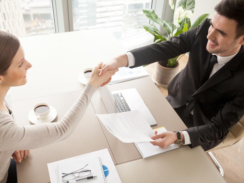 Un homme face à une femme à un bureau dans un contexte de travail. Ils se serrent la main.