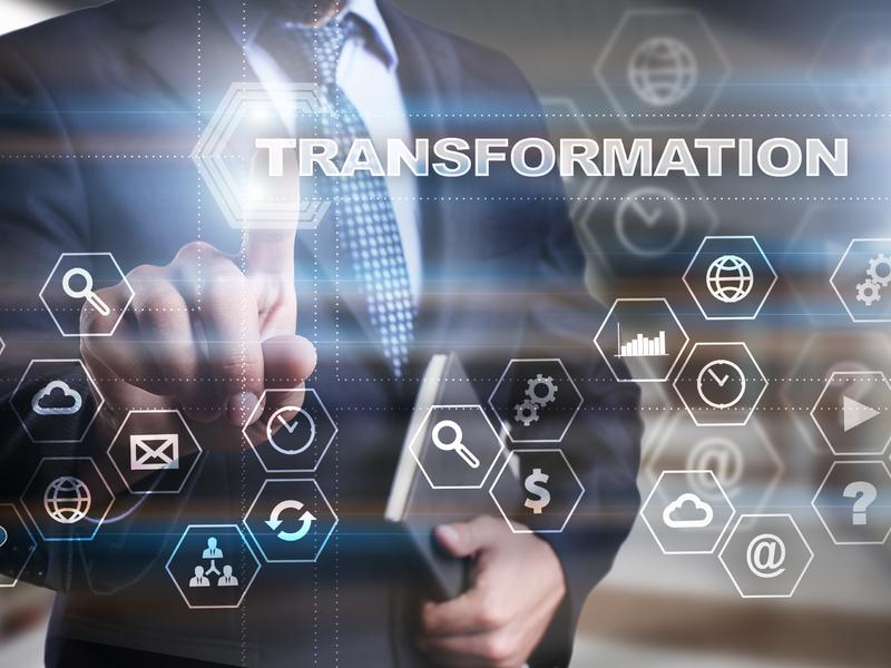 Un homme d'affaire devant un écran avec des logos interactifs, devant lui est inscrit transformation.