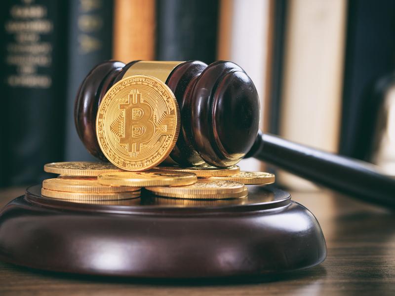 Un marteau de justice contre lequel sont posées des pièces de cryptomonnaies
