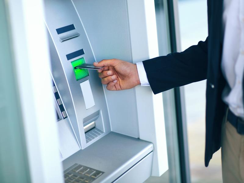 Un homme d'affaires retirant de l'argent à un ATM.