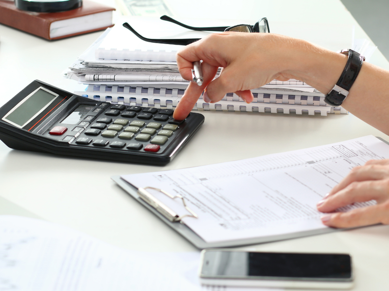 La main d'une femme tapant sur une calculette posée sur une table.