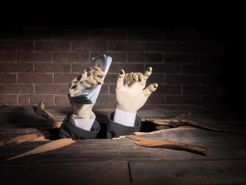 Deux mains de zombies dont une tenant des billets qui surgissent du sol.