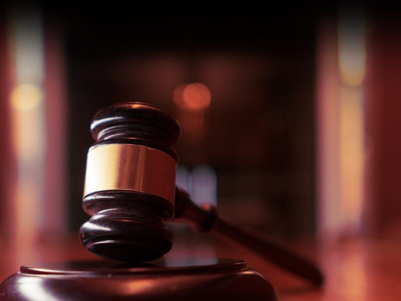 Un marteau de tribunal posé sur un bureau.