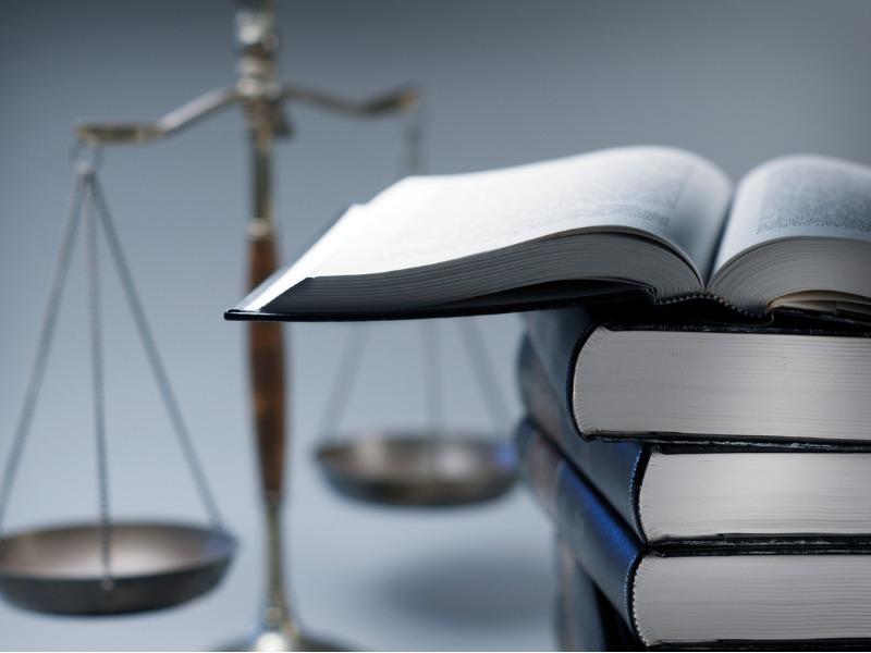 Une pile de livres dont le plus haut est ouvert. Derrière, on voit une balance de la justice.
