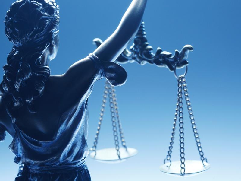 Une photo d'une statuette de la femme de la justice.