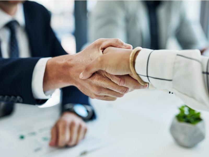 Une femme serrant la main à un homme.