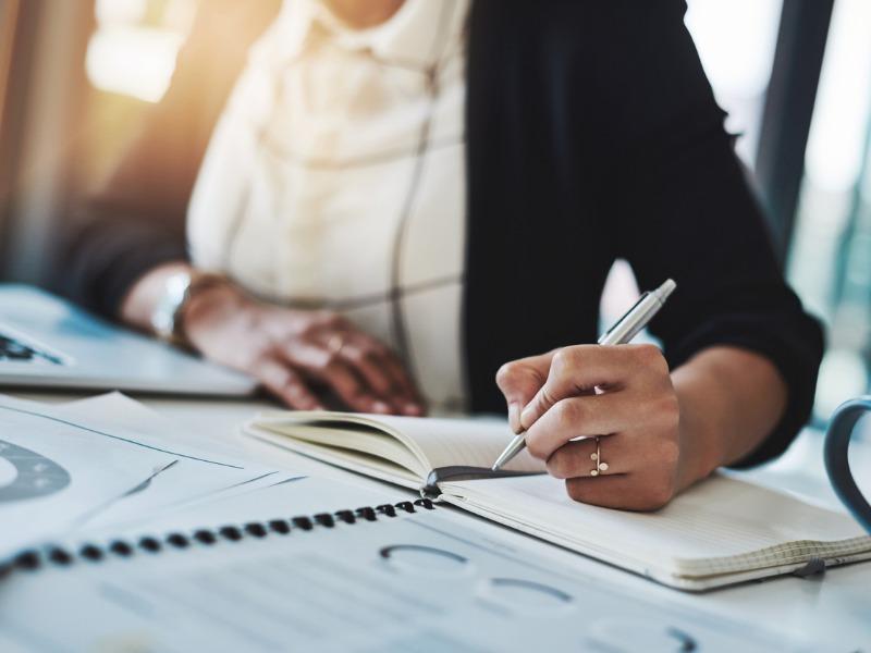 Une femme écrivant sur un cahier devant des graphiques financiers.