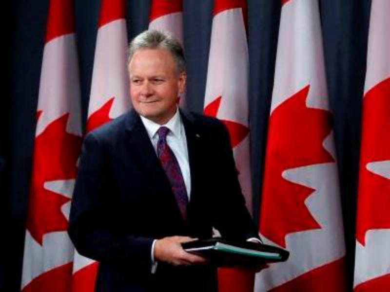Une photo de Stephen Poloz devant des drapeaux du Canada.