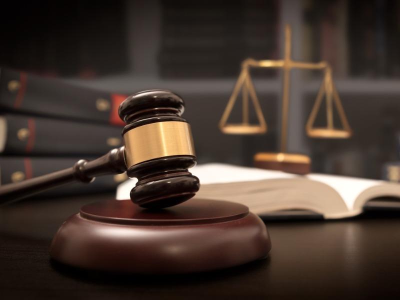 Un marteau pour le tribunal posé sur un bureau devant un livre ouvert et une balance de justice.