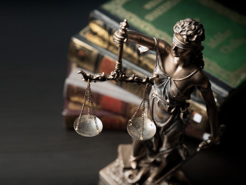Une statuette en bronze de la déesse de la justice devant une pile de livre.