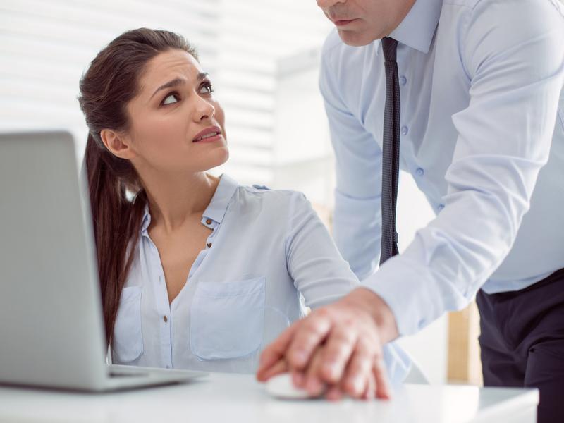 Une femme devant son ordinateur, qui regarde avec peur son collègue qui a posé sa main sur la sienne sur la souris.