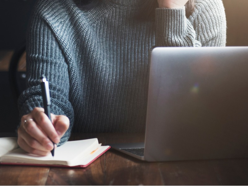 Une femme assise à un bureau devant un ordinateur. Elle écrit sur un bloc note.