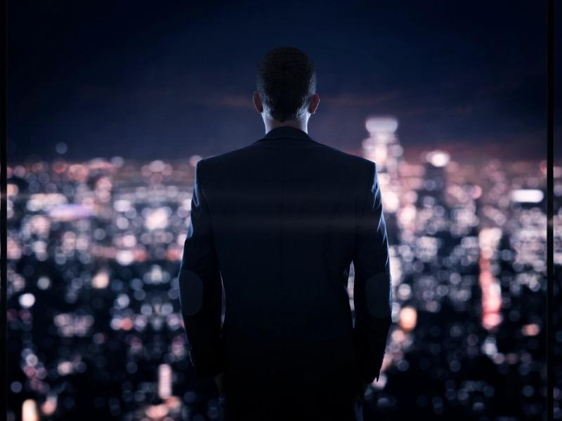Un homme d'affaire devant une fenêtre qui surplombe la ville.