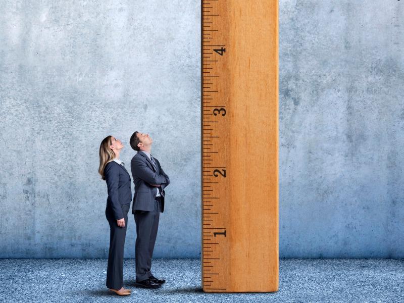 Un homme et une femme d'affaires, debout devant une règle géante.