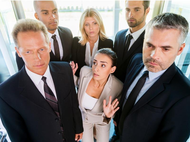Une femme d'affaires coincée dans un ascenseur avec d'autres hommes et femmes d'affaires.