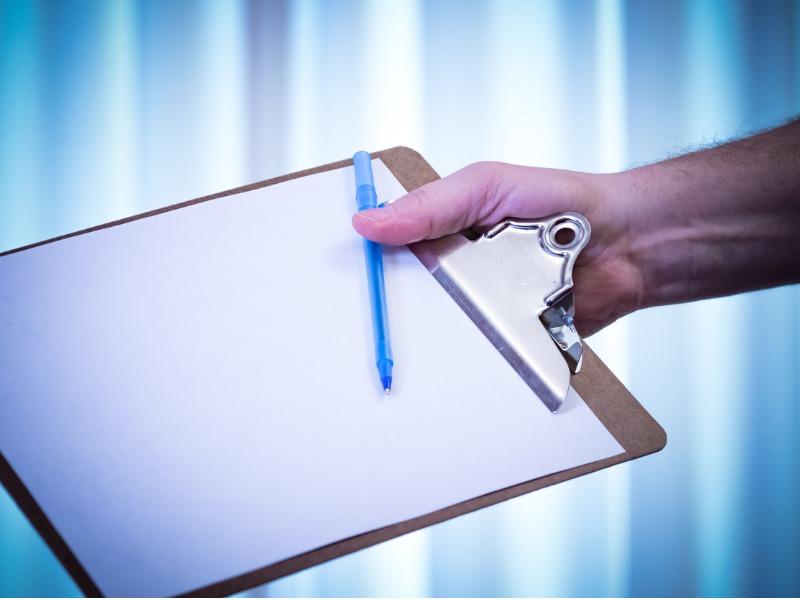 Une main tendant une plaquette en bois sur laquelle se trouve une feuille et un stylo.