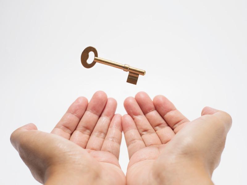Deux mains en coupe, une clé flotte au-dessus.