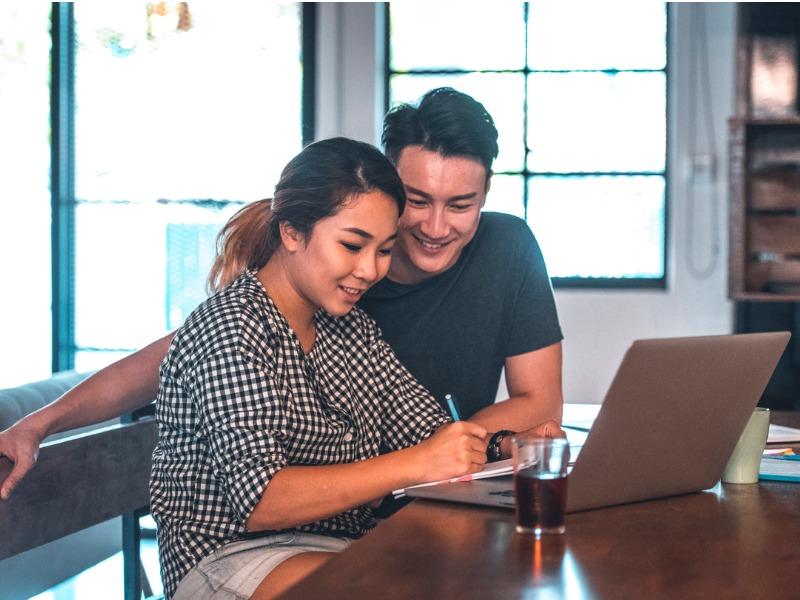 Un couple devant un ordinateur dans une maison. Ils ont l'air heureux.
