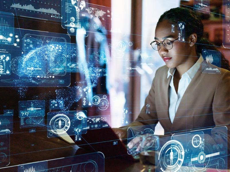 Une femme devant un ordinateur. En transparence on voit pleins d'applications technologiques, comme un logiciel de reconnaissance d'empreinte, etc.