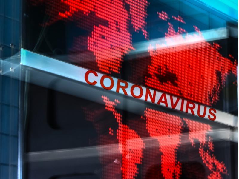 Une image de la carte du monde en rouge, devant laquelle est inscrite coronavirus.