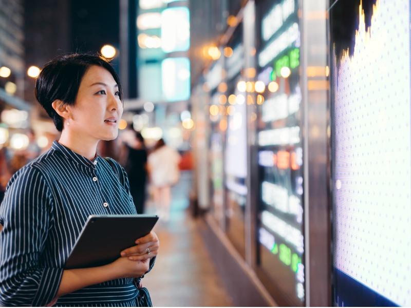 Une femme asiatique regardant un panneau représentant les cours du marché dans la rue.