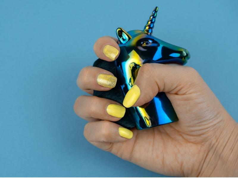 Une femme aux ongles jaunes qui tient une petite tête de licorne en plomb.