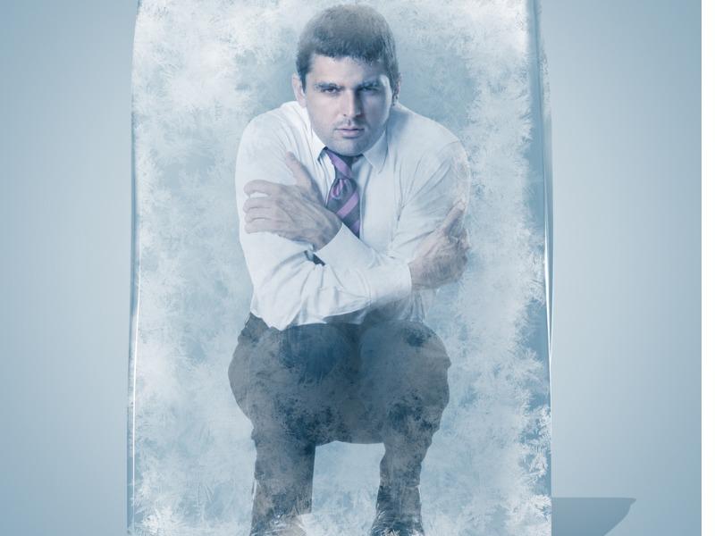 Un homme d'affaire accroupi, les bras autour de lui, figé dans un bloc de glace.