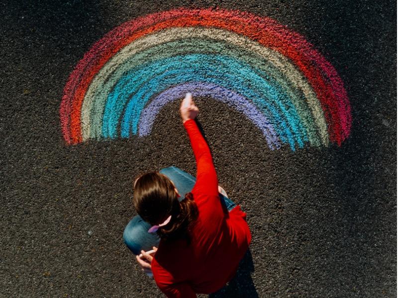 Une femme dessinant un arc-en-ciel sur le sol.