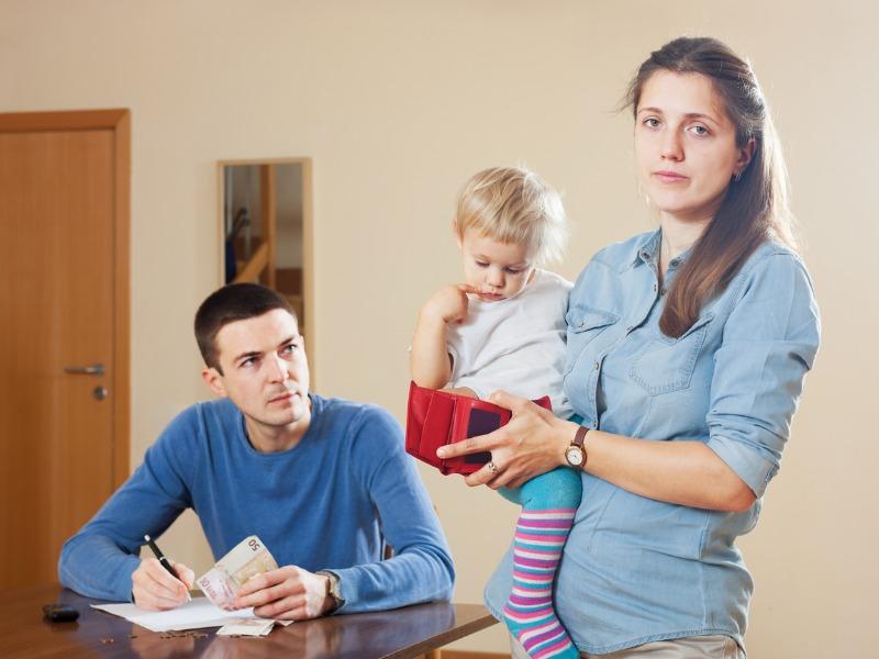 Une femme portant un bébé dans un bras, son portefeuille dans la main à côté de son mari qui écrit sur des papiers sur une table.
