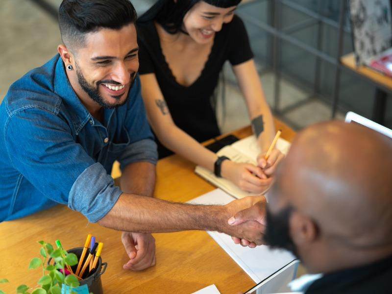 Un homme d'affaire à un bureau serrant la main d'un client, alors que la femme de celui-ci signe des papiers.