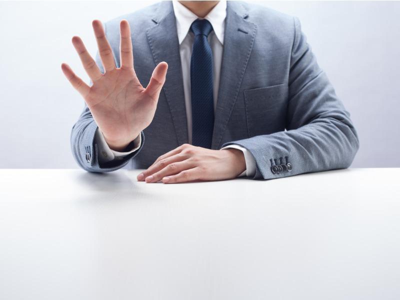 Un homme d'affaire montrant 5 doigts.