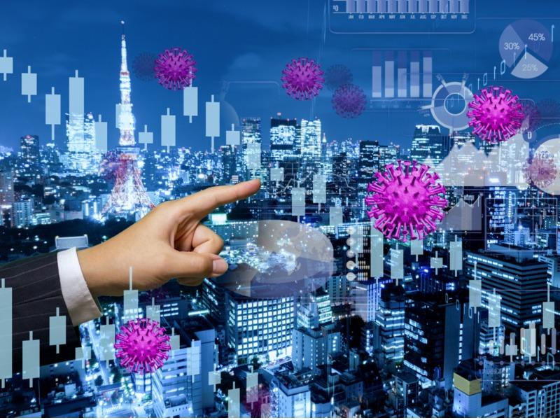 Un homme d'affaires montrant un graphique en transparence sur une ville. Autour on voit pleins de petits virus de COVID-19.