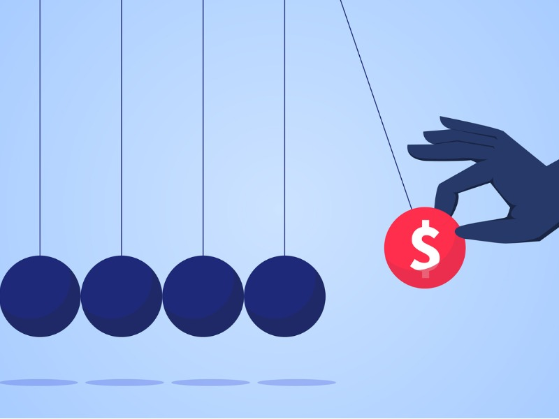 Une main d'homme d'affaires levant une boule représentant un dollar pour qu'elle frappe d'autres boules.