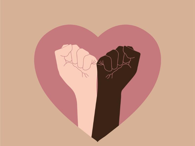 Une main noire et une main blanche cote à cote levant le poing dans un coeur.