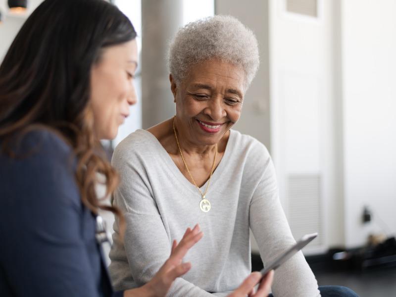 Une conseillère montre quelque chose sur son téléphone à sa cliente.
