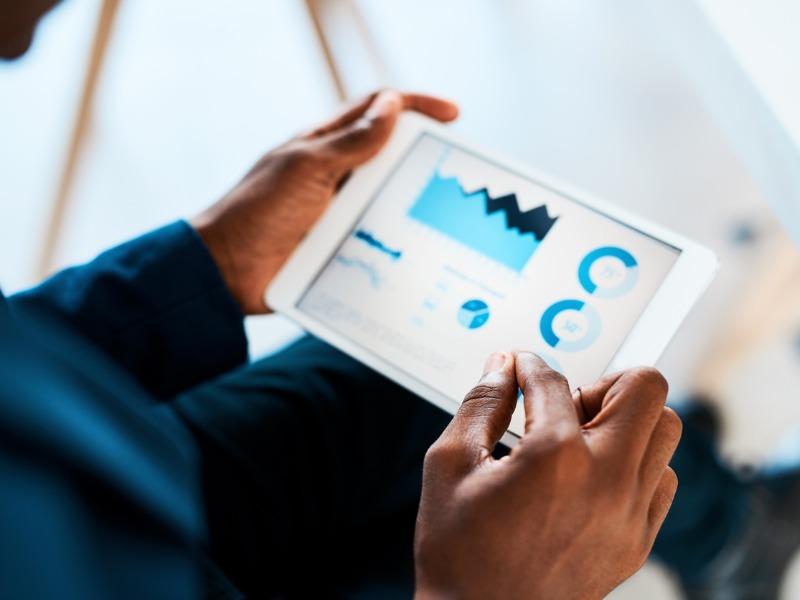 Un homme de couleur regarde des graphiques financiers sur une tablette.