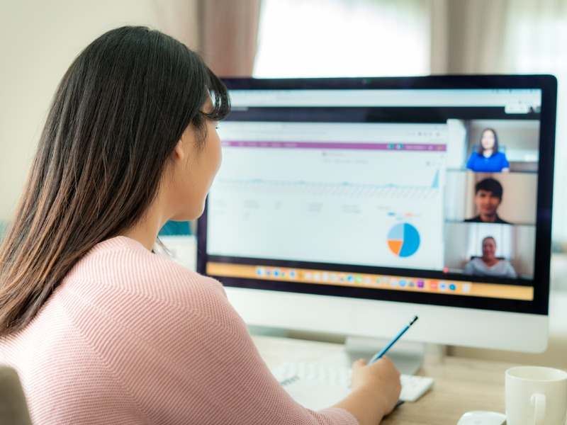 Une femme faisant du télétravail en skypant avec ses collègues.