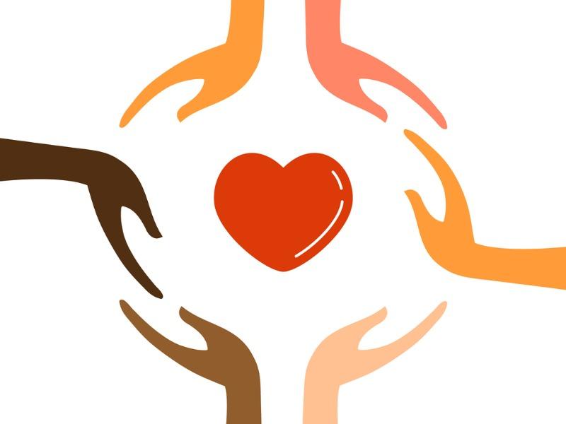 Des mains de plusieurs couleurs formant un cercle autour d'un coeur