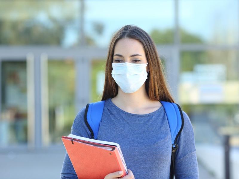 Une étudiante portant un masque pour se protéger de la COVID-19.