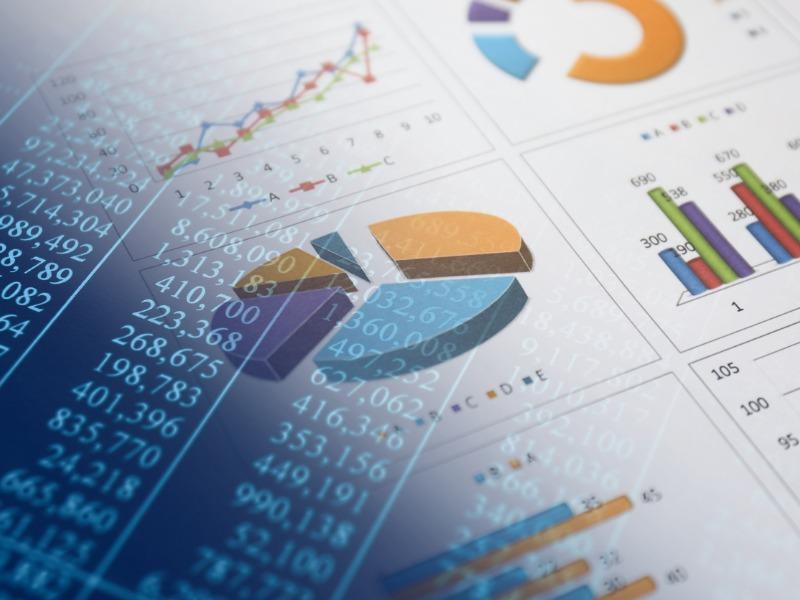 Une feuille de résultats financiers, par-dessus, des chiffres apparaissent en transparence.
