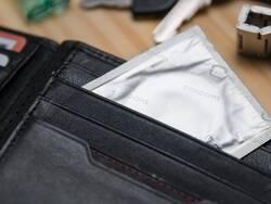 Un préservatif dépassant d'un portefeuille