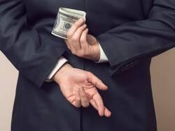 Un homme d'affaire cachant un billet dans son dos et croisant les doigts de son autre main.