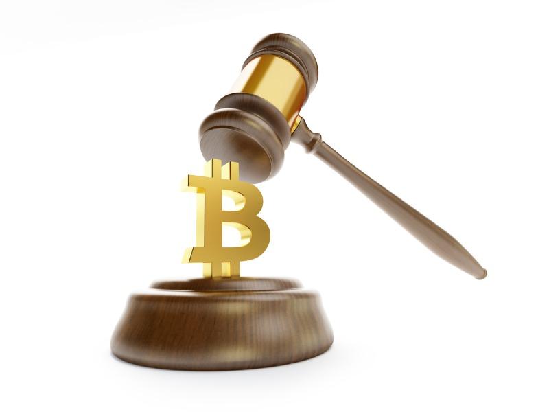 Un marteau de tribunal écrasant un bitcoin.
