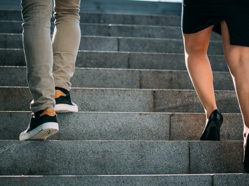 Une femme et un homme grimpant les escaliers. La femme est une marche en dessous de l'homme.